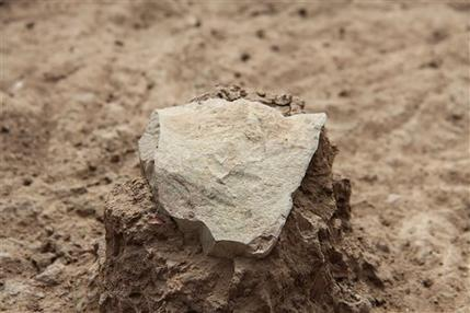 This undated photo made available in May 2015 by the Mission Prehistorique au Kenya - West Turkana Archaeological Project shows the excavation of a stone tool found in the West Turkana area of Kenya. This and other artifacts, dated at 3.3 million years old, are much older than the earliest known trace of our own branch of the evolutionary family tree. So it's a new challenge to the traditional idea that only members of our branch made stone tools. The discovery was reported in the journal Nature on Wednesday, May 20, 2015. (MPK-WTAP via AP)